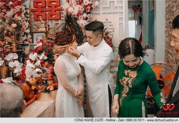 Mẹ chú rể đeodây chuyền cho cô dâu và được chú rể hổ trợ
